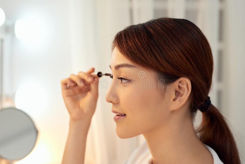 Sluiting van een mooie Aziatische vrouw die zwarte Mascara op Eyelashes gooit Beauty Cosmetics stock afbeelding