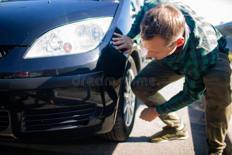 Sluiting van een volwassen man die krassen op zijn auto bekijkt royalty-vrije stock afbeelding