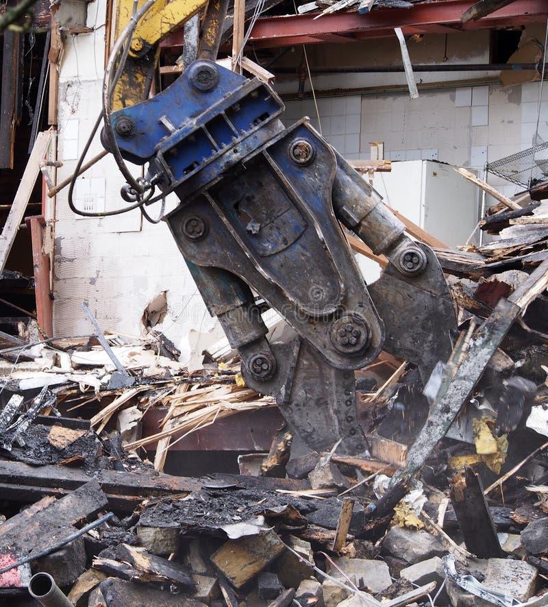 sluiting van een zware sloopklauw die puin en puin op een bouwplaats ophaalt stock afbeelding