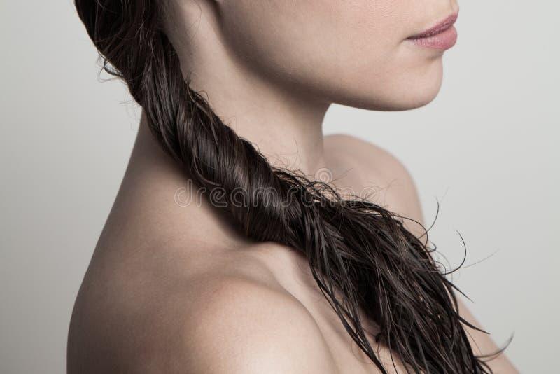 Sluiting van jonge vrouw nat verdraaid haar natuurschoon concept royalty-vrije stock afbeelding