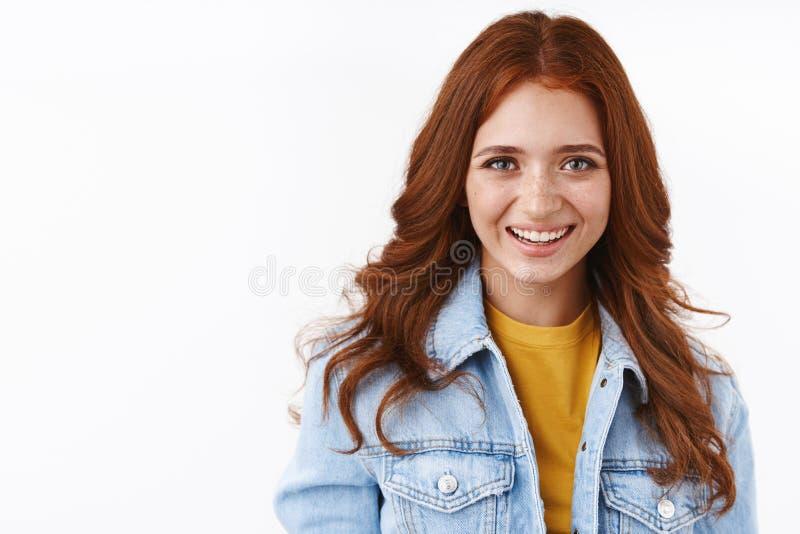 Sluiting van vrolijke, mooie vrouwelijke studente met freckles in denim jack boven geel t-shirt, glimlachend vrolijk en vrolijk stock afbeeldingen