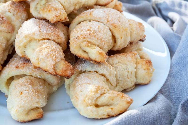 Sluitingsweergave van rotte, suiker-gefronste croissants van een kruldeeg dat ligt op een witte plaat naast een grijze doek Zoete stock foto's