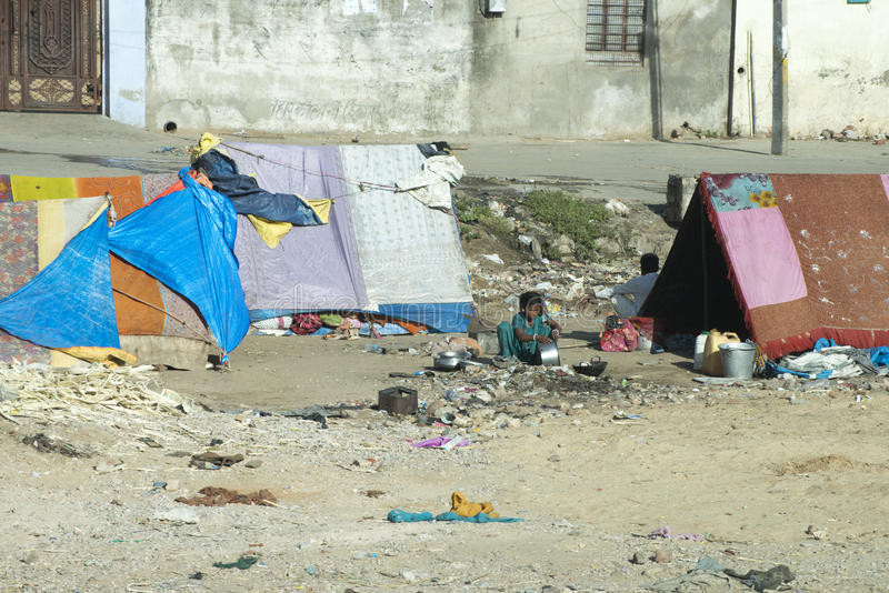Slum Camp, Poor and Poverty in India. Poor people trapped in poverty in India tend to daily chores and cooking while living in a slum camp in India. The brutal royalty free stock image