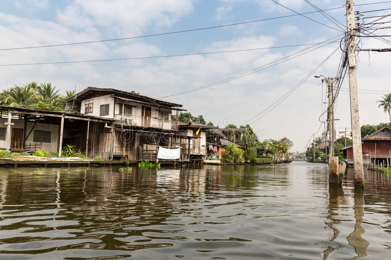 Slum on dirty canal in Thailand. Houses made out of scavenged materials on canal (Thailand stock photo