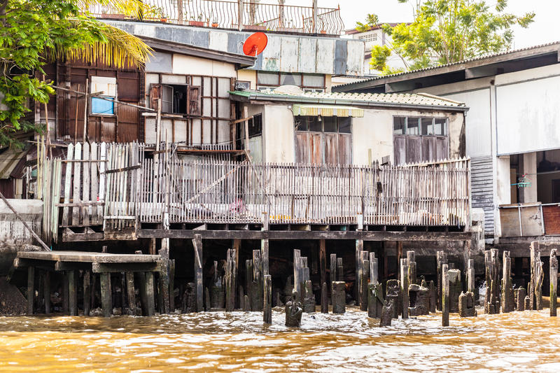 Slum on stilts. Wooden slums on stilts on the riverside of Chao Praya River in Bangkok, Thailand stock image