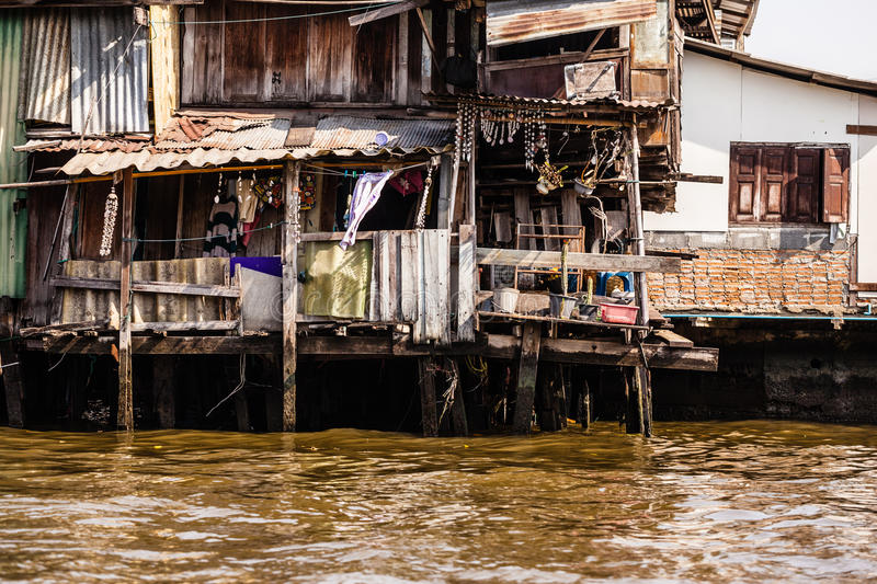 Slum on water. Wooden slums on stilts on the riverside of Chao Praya River in Bangkok, Thailand royalty free stock photography