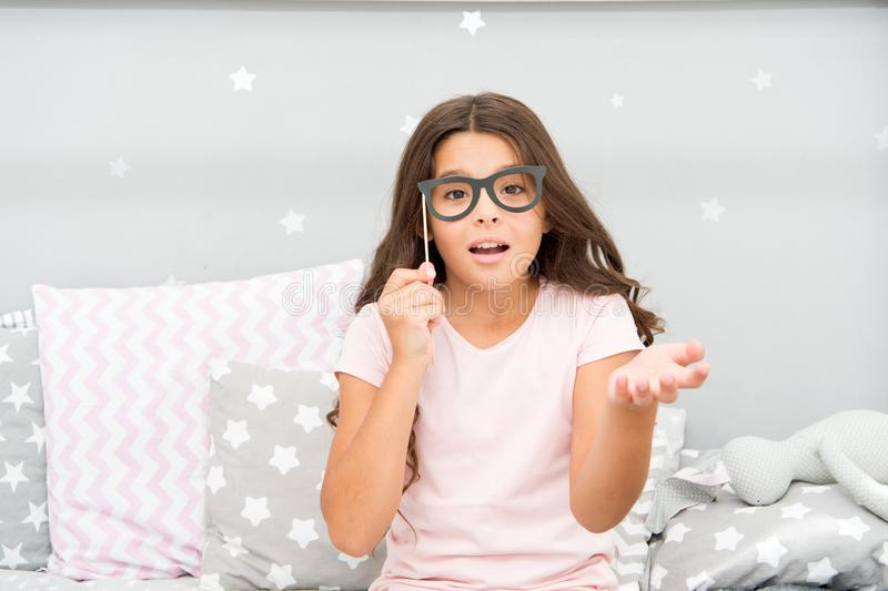 Slumber party photo booth props. Kid girl wondering posing with vintage eyeglasses party attribute. Prepare photo booth royalty free stock photo