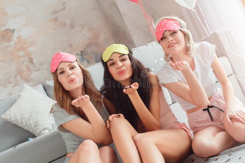 Slumber Party. Young women in sleeping mask together at home sitting on floor sending kiss to camera happy. Young diverse women wearing sleeping mask having stock photo