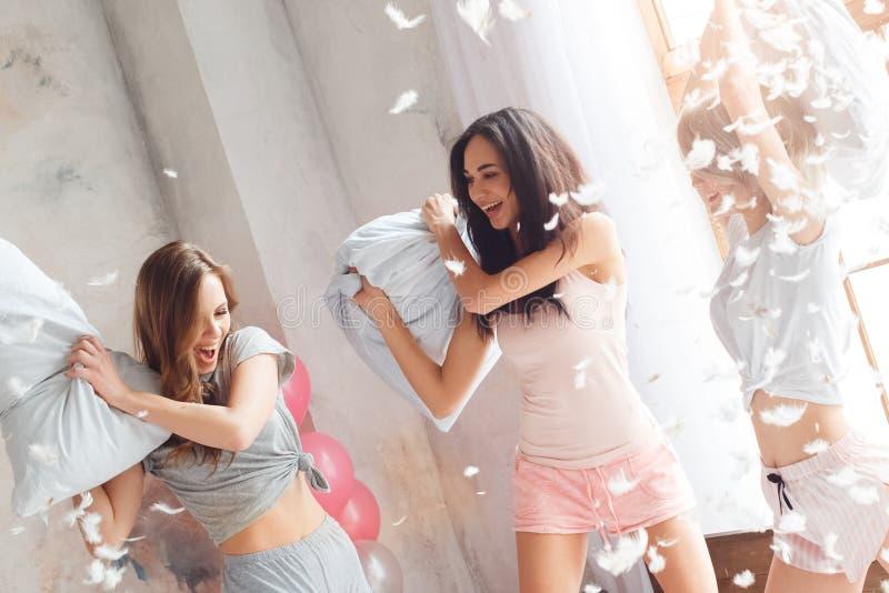 Slummerparti Unga kvinnor som har tillsammans gyckel på säng som har kuddekampen som skrattar skämtsam närbild arkivbild