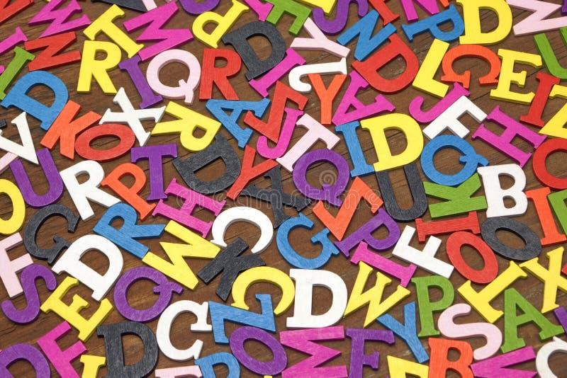 Slumpmässiga engelska trämångfärgade bokstäver på den bruna träBacen arkivbilder