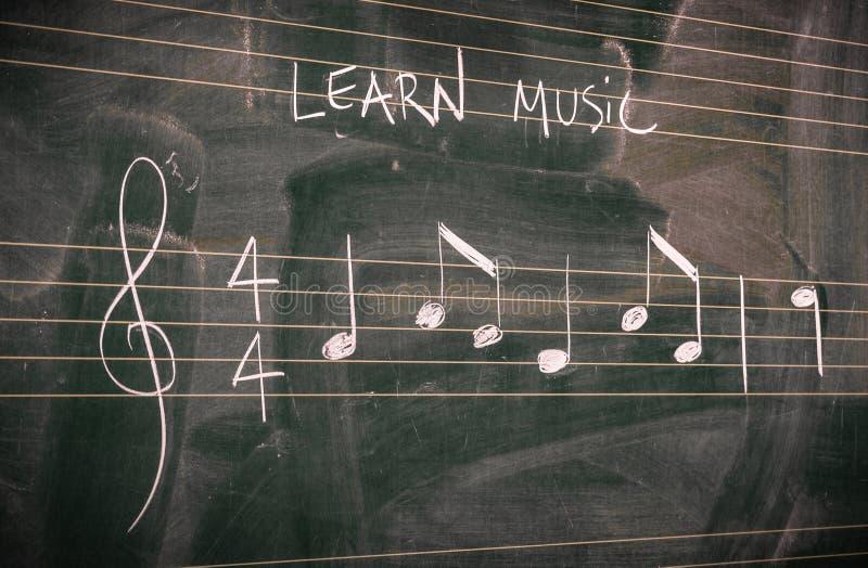 Slumpmässiga musikanmärkningar som är skriftliga på en svart tavla Lär eller undervisa musikbegrepp royaltyfria foton