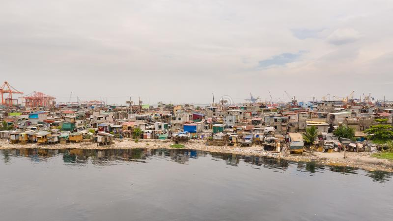 Slums in Manila near the port. Houses of poor inhabitants. A lot of garbage in the water, Philippines, top view royalty free stock photos