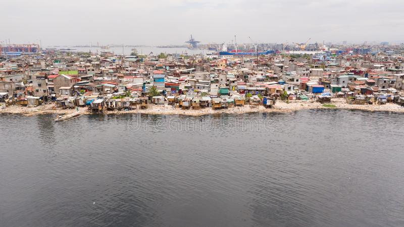 Slums in Manila near the port. Houses of poor inhabitants. A lot of garbage in the water, Philippines, top view royalty free stock photography
