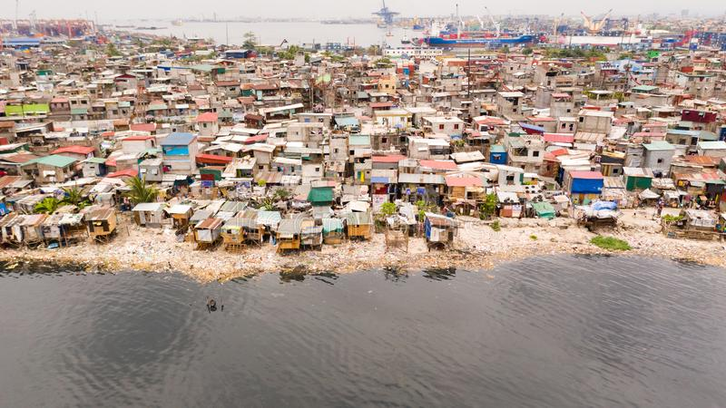 Slums in Manila near the port. Houses of poor inhabitants. A lot of garbage in the water, Philippines, top view stock photo