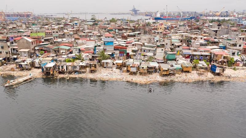 Slums in Manila near the port. Houses of poor inhabitants. A lot of garbage in the water, Philippines, top view royalty free stock photo