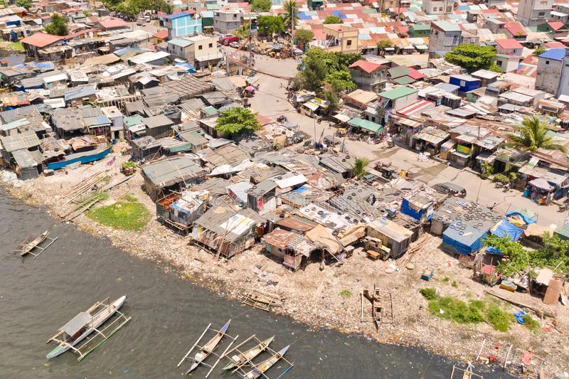 Slums in Manila, a top view. Houses of poor people and boats in poor areas. Sea pollution by household waste. Plastic trash on the beach royalty free stock photo