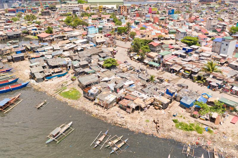 Slums in Manila, a top view. Houses of poor people and boats in poor areas. Sea pollution by household waste. Plastic trash on the beach royalty free stock photos
