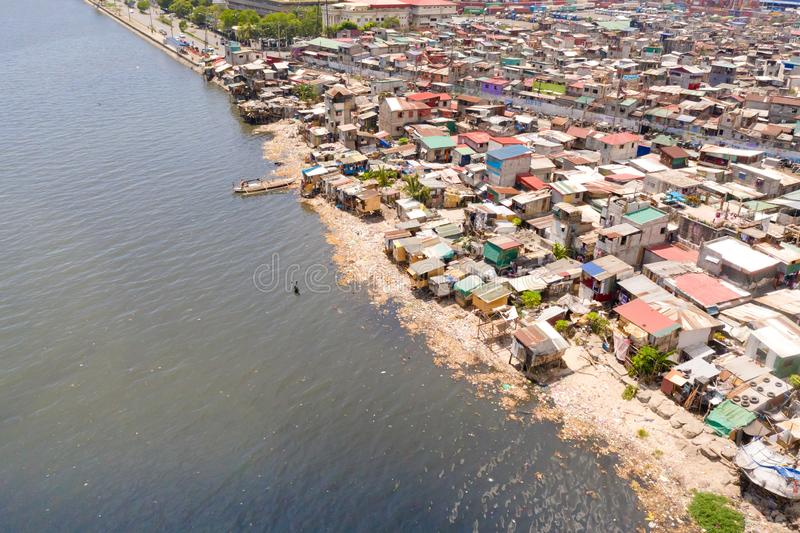 Slums in Manila, a top view. Sea pollution by household waste. Plastic trash on the beach royalty free stock images