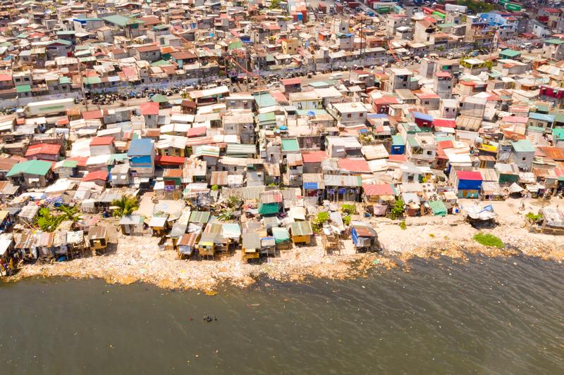 Slums in Manila, a top view. Sea pollution by household waste. Plastic trash on the beach royalty free stock image