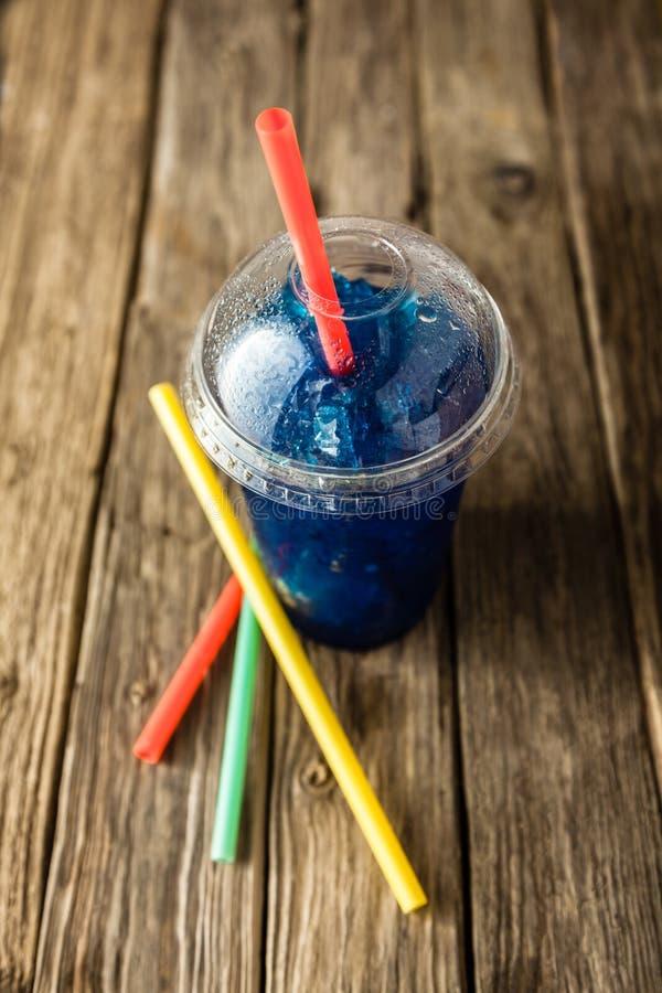 Slushie blu congelato in tazza di plastica con le paglie fotografie stock