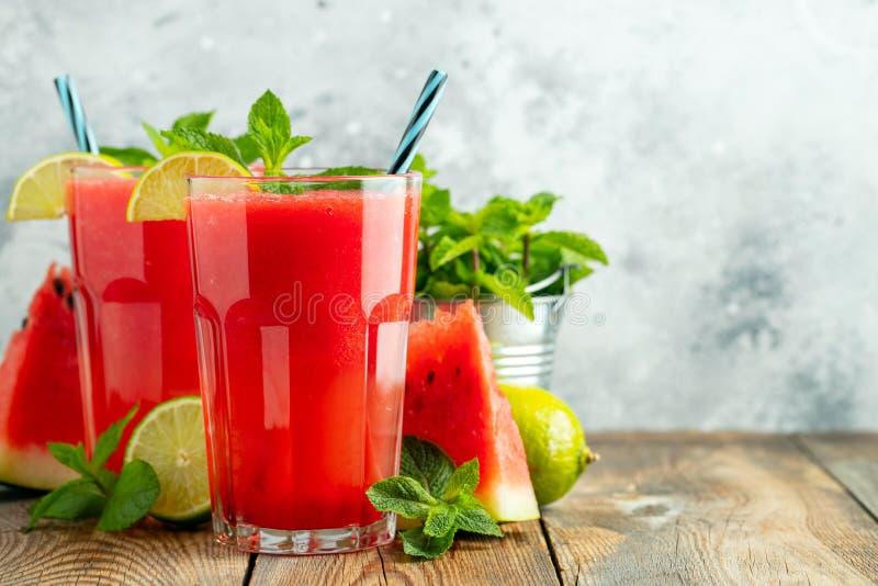 Slushie dell'anguria con calce e la menta, bevanda di rinfresco di estate in vetri alti su un fondo blu-chiaro Freddo dolce fotografia stock libera da diritti