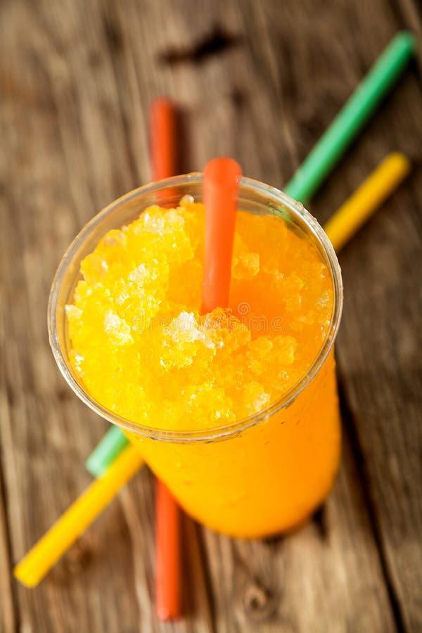 Slushie orange congelé dans la tasse en plastique avec la paille photographie stock