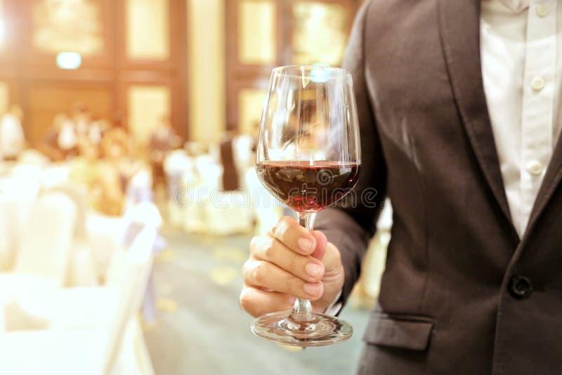 Slut av av den bärande dräkten för affärsman som rymmer ett exponeringsglas av vin i företagspartiet med gult ljus för stråle i b royaltyfri fotografi