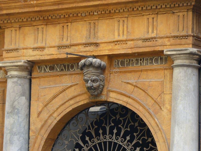Slut av en dörr av en forntida slott i Palermo med över huvudet av en gamal man med en hatt, Sicilien, Italien royaltyfri bild