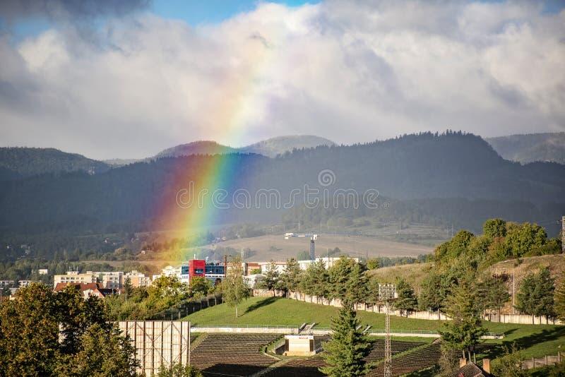 Slut av en regnbåge i himlen över staden i solig dag royaltyfri foto