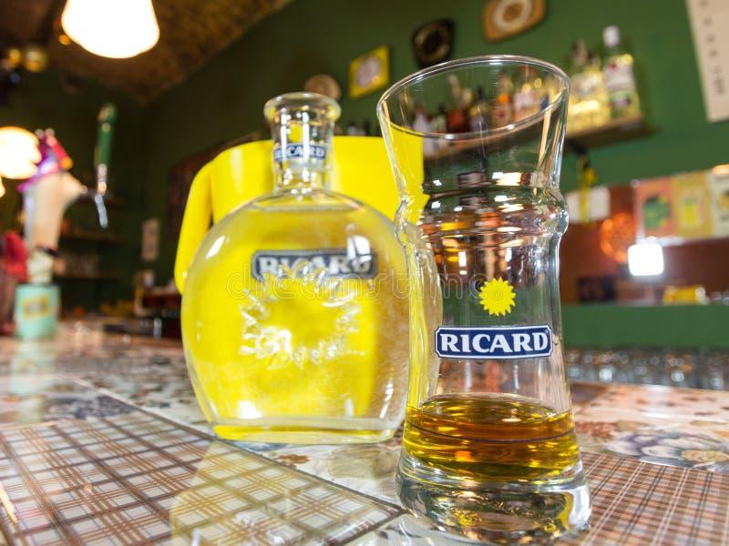 Slut av på en Ricard tillbringare och en vattenflaska med dess logo Ricard är pastis, en anis och lakritsen smaksatte aperitif royaltyfri bild