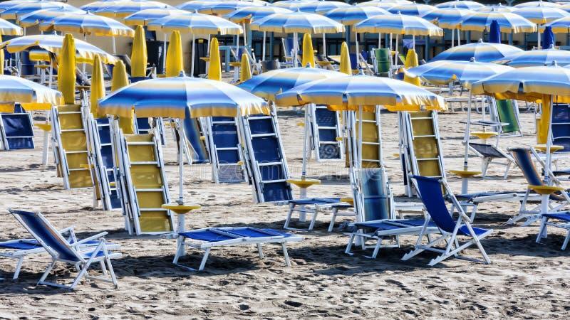Slut av sommar - slags solskydd och soldagdrivare stängde sig på stranden royaltyfri foto