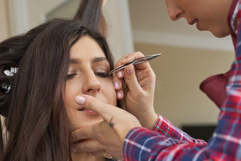 Slut för ögonfransborttagningstillvägagångssätt upp Härlig kvinna med långa snärtar i en skönhetsalong Ögonfransförlängning royaltyfri bild
