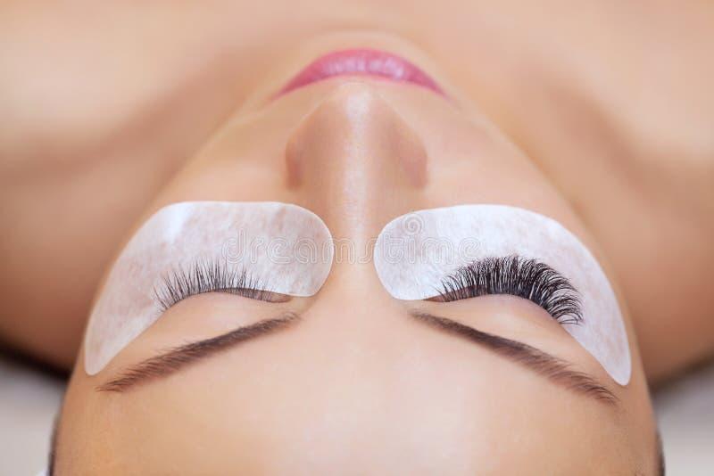 Slut för ögonfransborttagningstillvägagångssätt upp Härlig kvinna med långa snärtar i en skönhetsalong fotografering för bildbyråer