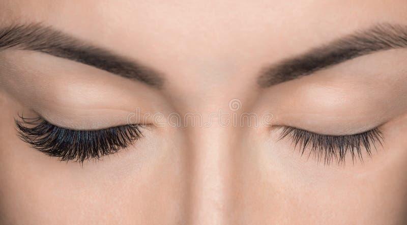 Slut för ögonfransborttagningstillvägagångssätt upp Härlig kvinna med långa snärtar i en skönhetsalong royaltyfri foto