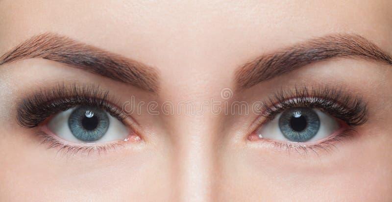 Slut för ögonfransborttagningstillvägagångssätt upp Härlig kvinna med långa snärtar i en skönhetsalong arkivfoton