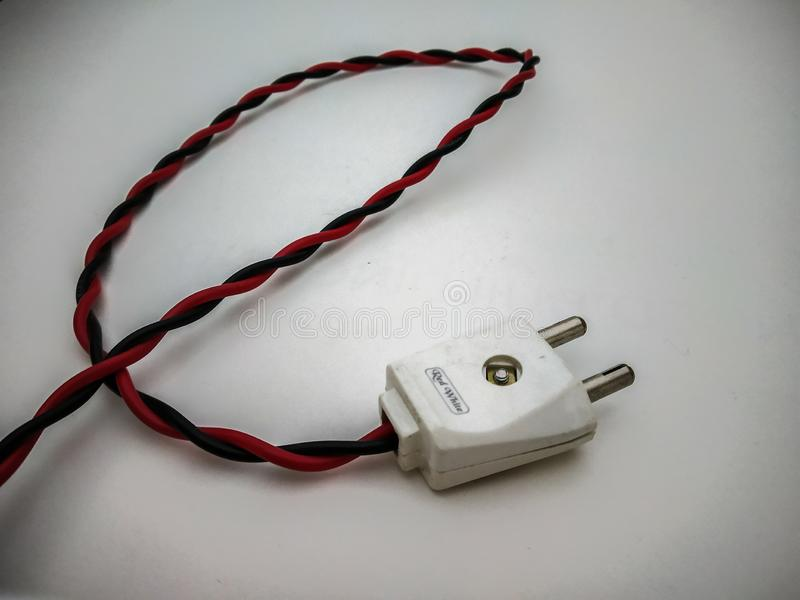slut för elektrisk propp upp skott med röd tråd i en vit bakgrund arkivbild
