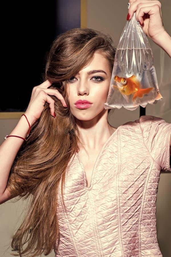Slut för fece för kvinna för modemodell upp Framsidakvinna med lycklig sinnesrörelse Sinnlig flicka med den guld- fisken i plastp royaltyfria bilder