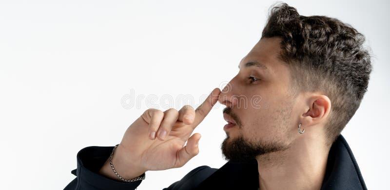 Slut f?r sidosikt upp st?enden av den unga sk?ggiga mannen som som trycker p? hans n?sa med fingret som isoleras ?ver vit bakgrun royaltyfri bild