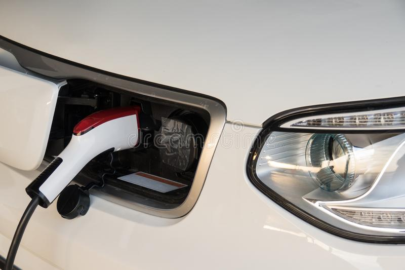 Slut som laddar upp ett elbilbatteri Elbil på uppladdningsstationen med tillförselen för maktkabel som in pluggas royaltyfri foto