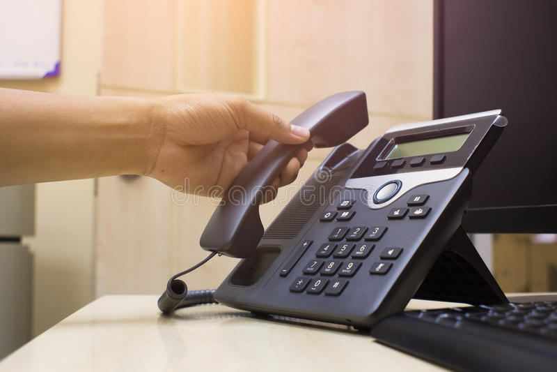 Slut som rymmer upp förestående telefonen på kontorsskrivbordet, kontorstelefon och dator och tangentbord arkivbilder