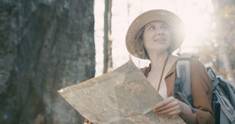 Slut upp attraktiv ung kvinna i stilfull hatt och en turist- översikt i hennes händer som omkring ser arkivbild