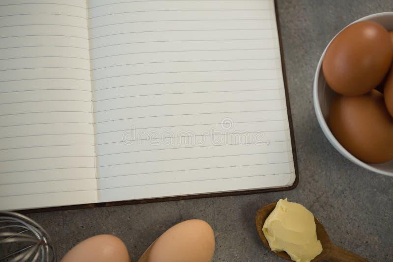 Slut upp av ägg vid den öppna boken fotografering för bildbyråer