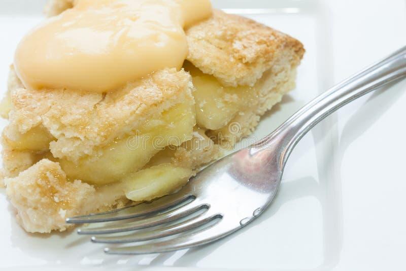 Slut upp av äppelpajen och vaniljsås arkivbild
