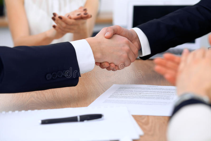Slut upp av affärsfolk som skakar händer på mötet eller förhandling i kontoret Partners tillfredsställs därför att royaltyfri foto
