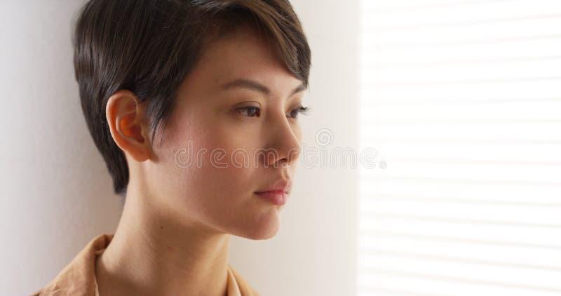 Slut upp av allvarlig asiatiska kvinnas framsida fotografering för bildbyråer