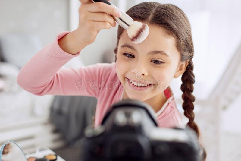 Slut upp av att le flickan som applicerar pulver till hennes panna arkivfoto