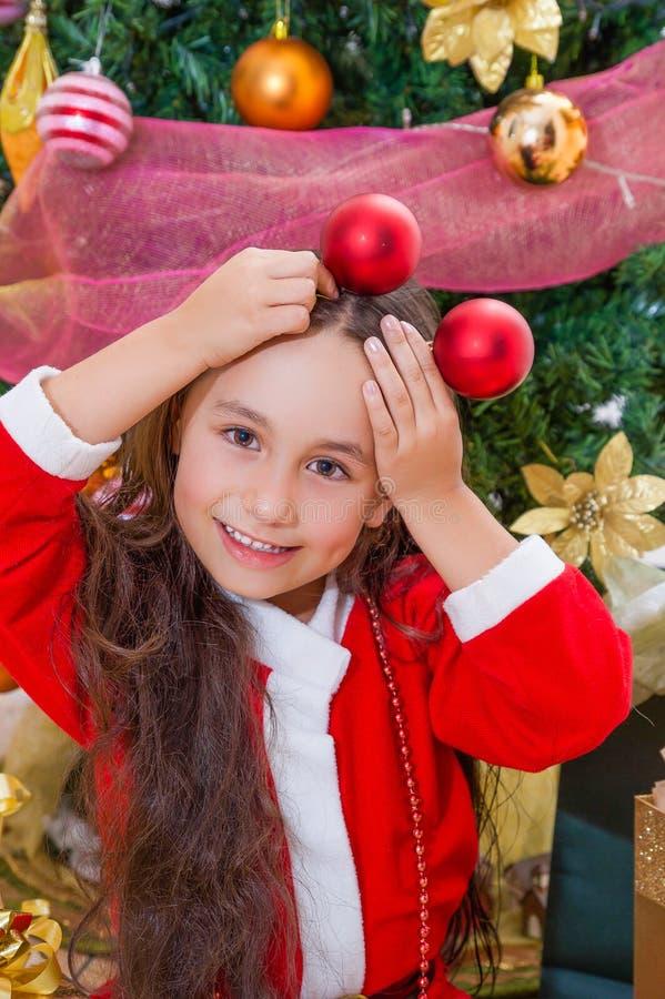 Slut upp av att le flickan som bär bollar för jul för en röd för santa dräkt och innehav två i hennes händer och poserar över hen fotografering för bildbyråer