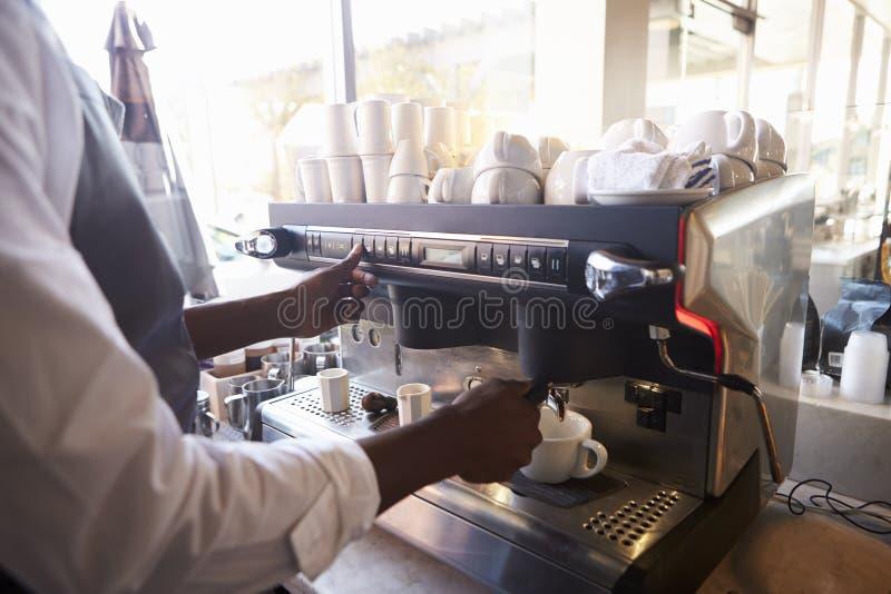 Slut upp av Barista Making Coffee In delikatessaffär genom att använda maskinen royaltyfria bilder
