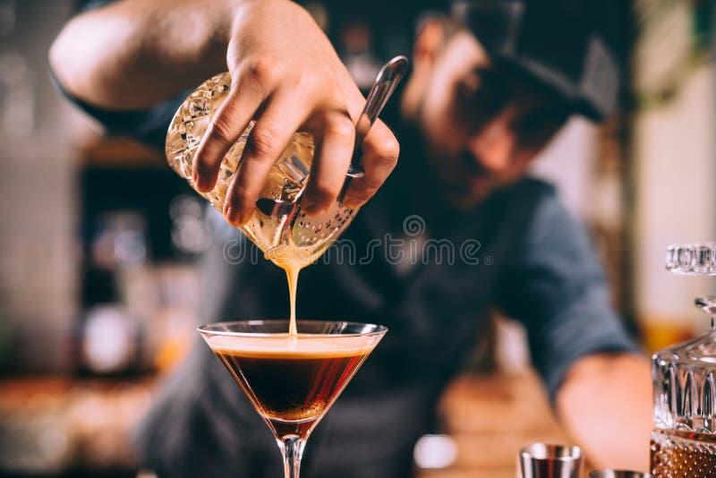 Slut upp av bartenderhanden som häller den alkoholiserade coctailen i martini exponeringsglas royaltyfria foton