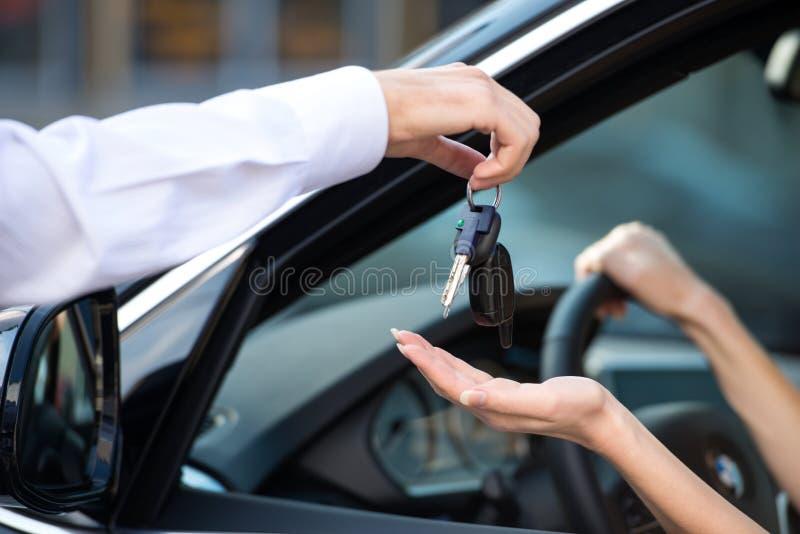 Slut upp av bilåterförsäljaren som ger tangenter till kvinnan arkivbild